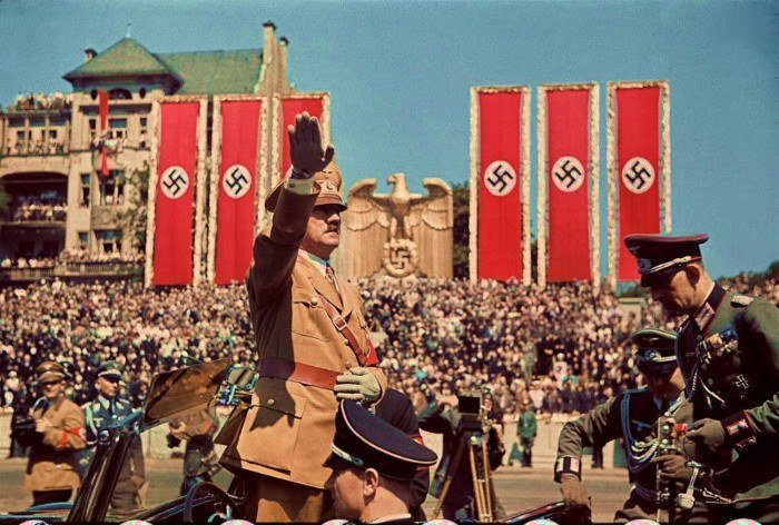 Hitler saluting with swastikas on the back
